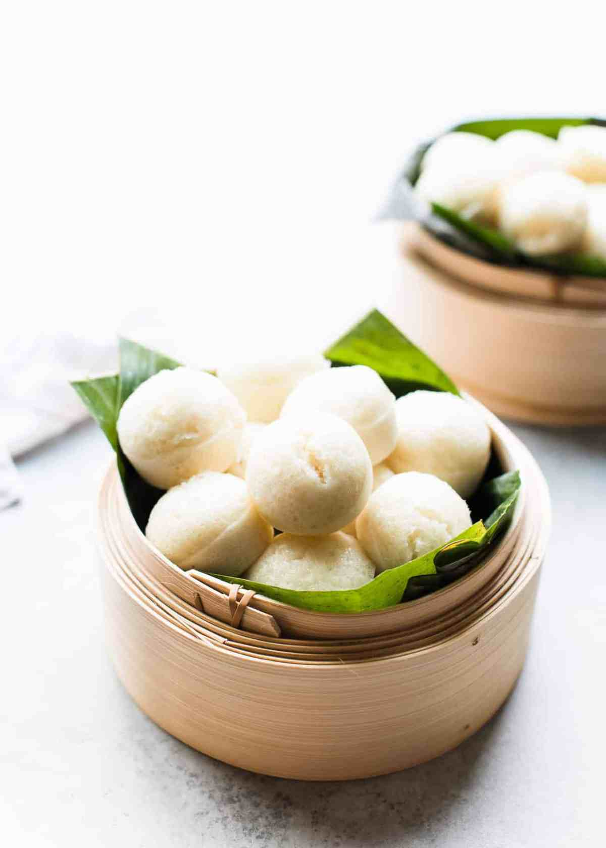 Mini steamed rice cakes, or puto, in a bamboo steamer.