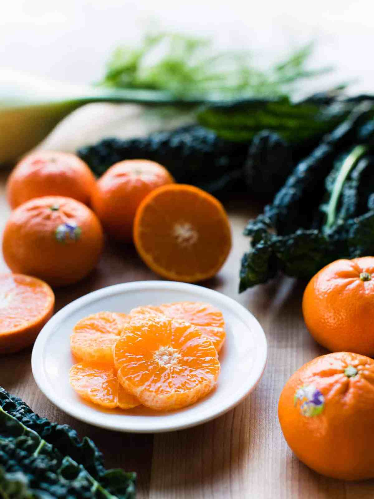 slices of Halos Mandarin Oranges on a white plate with kale in the background