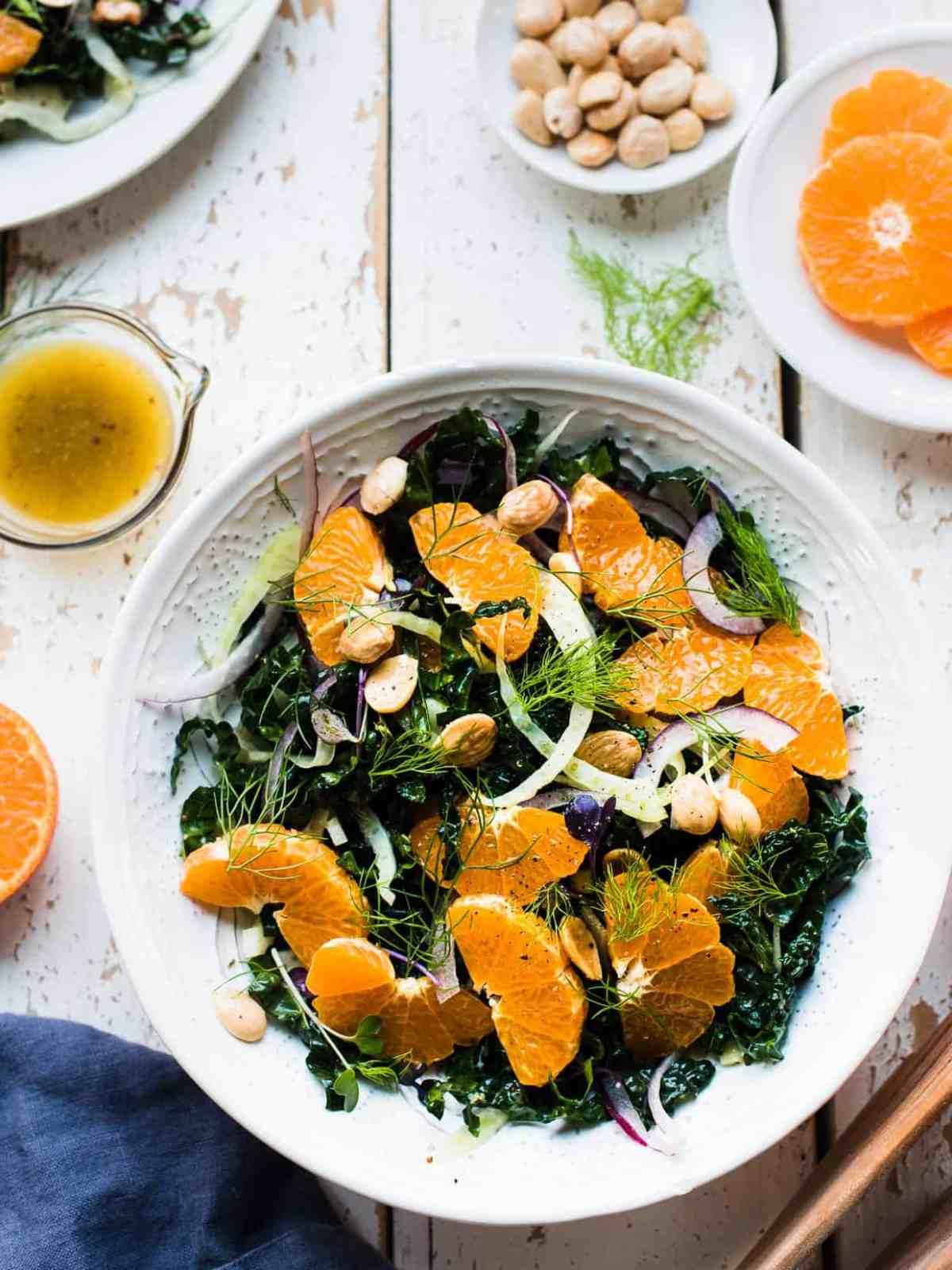 overhead shot of kale salad with mandarin oranges, fennel, marcona olives and orange vinaigrette on the side