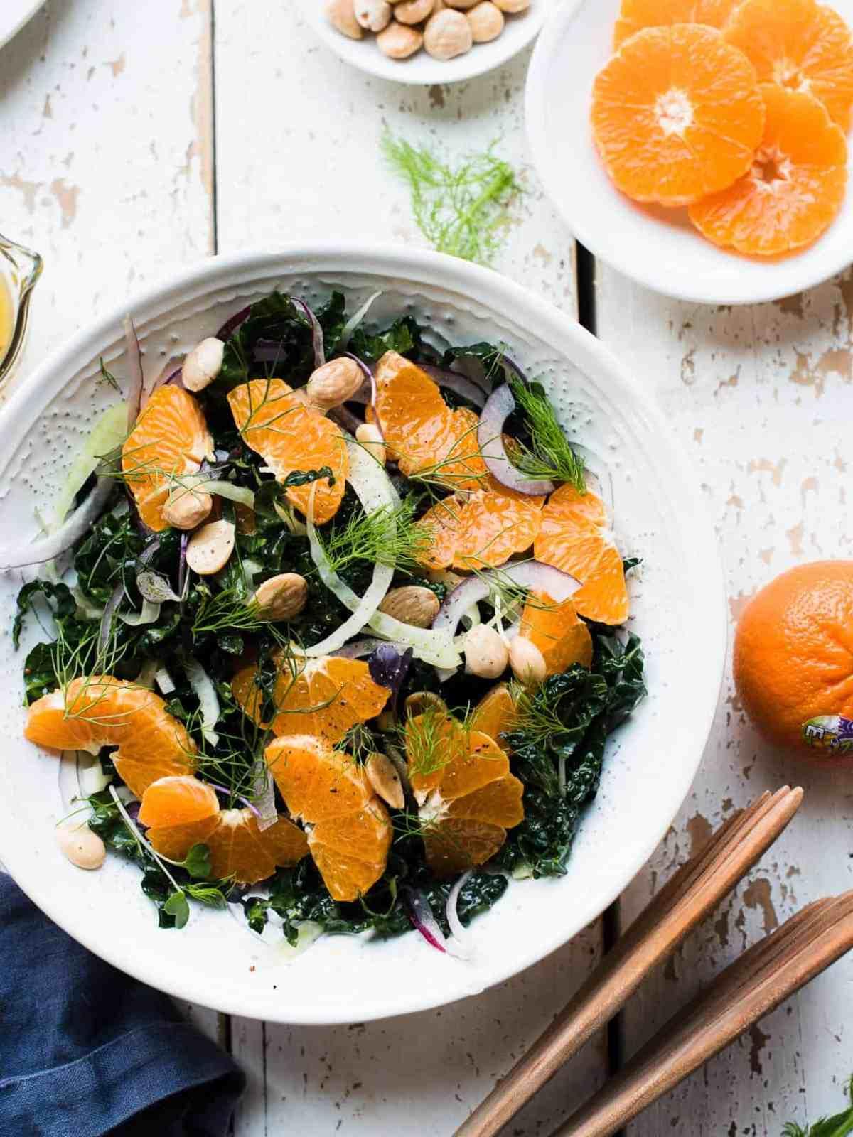 Over head shot of mandarin orange kale salad with salad tongs on the side.