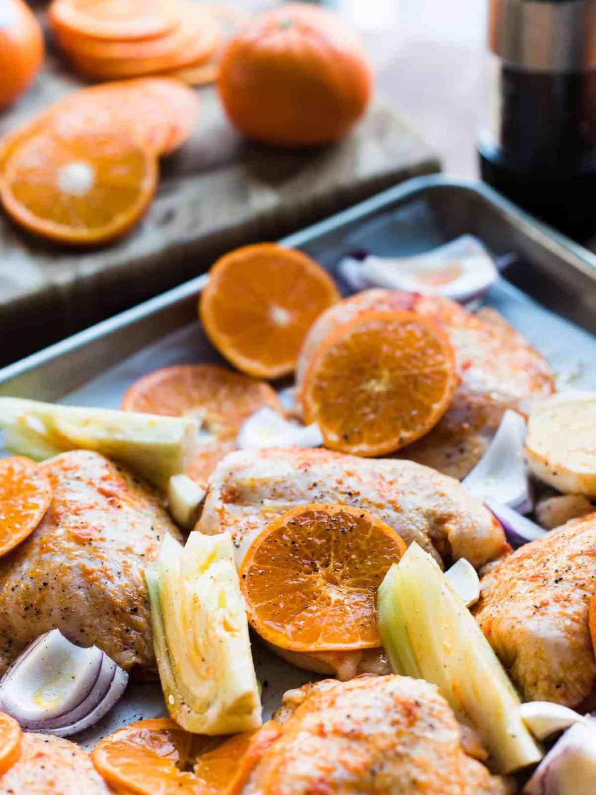 Preparing chicken thighs with mandarin orange slices, fennel, red onion on baking sheet.