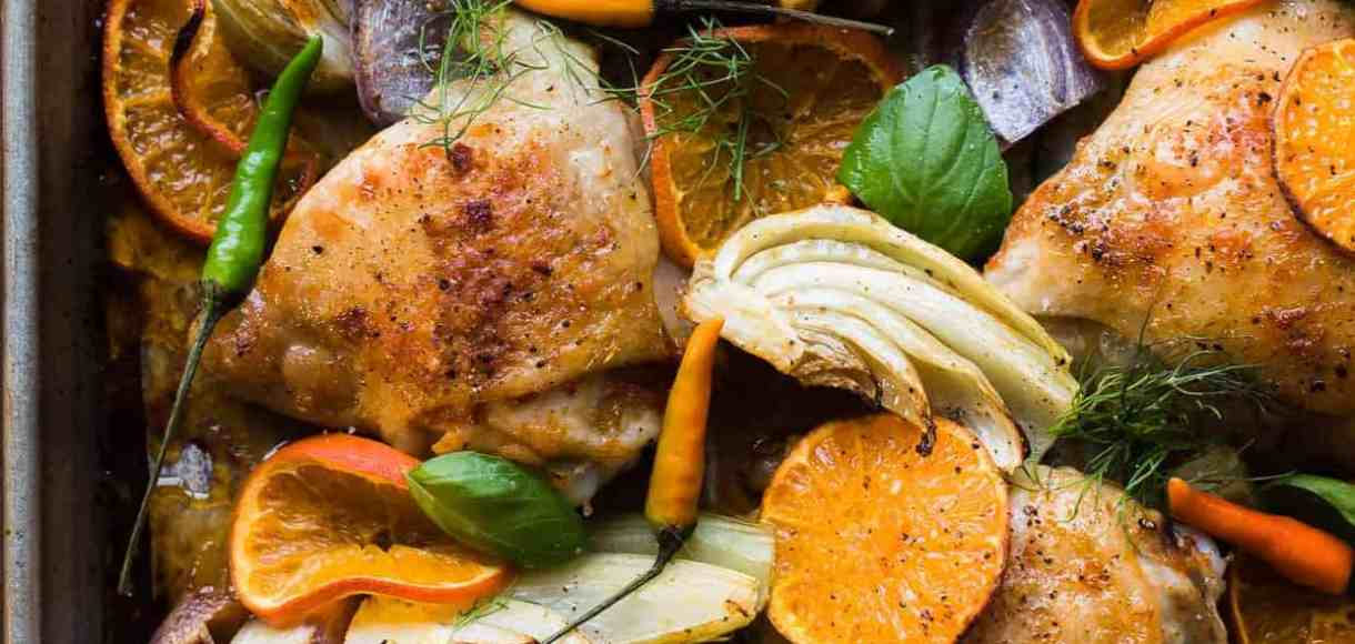 Thai-Spiced Mandarin Orange Roasted Chicken Thighs with thin slices of mandarin oranges, fennel, onion and garlic on a sheet pan.