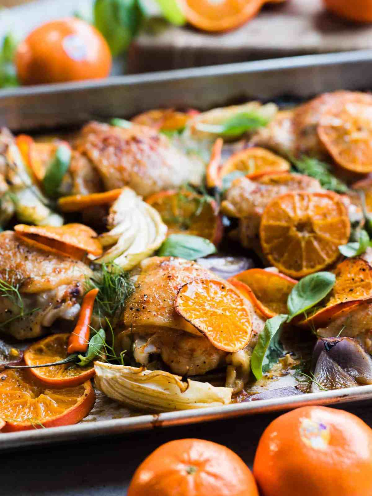 Thai-Spiced Mandarin Orange Roasted Chicken Thighs on a baking sheet with slices of orange, fennel and onion.