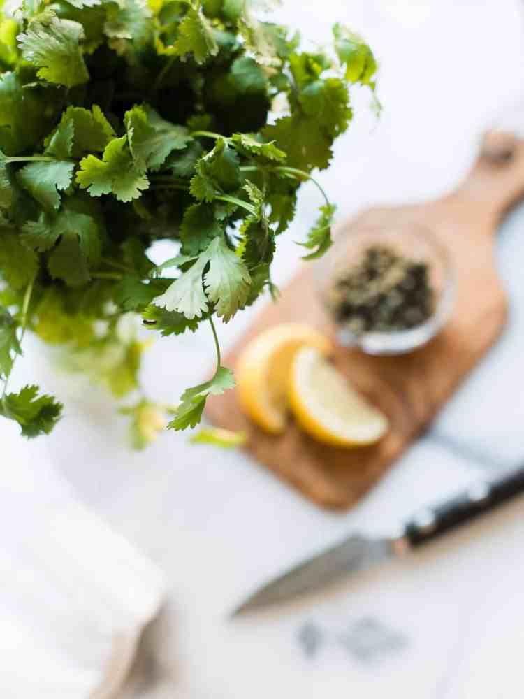 Fresh cilantro with lemons and capers in the background.