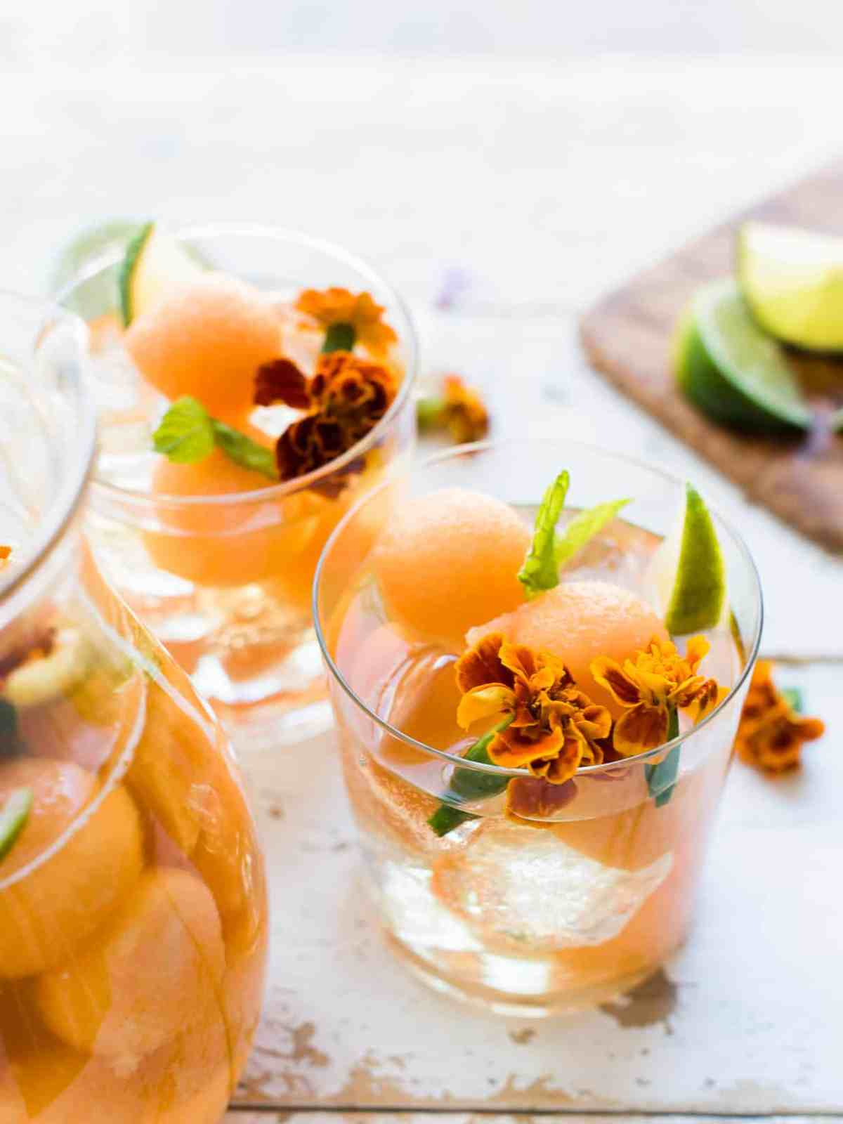 Glasses of Ginger Cantaloupe Sangria garnished with mint and edible flowers