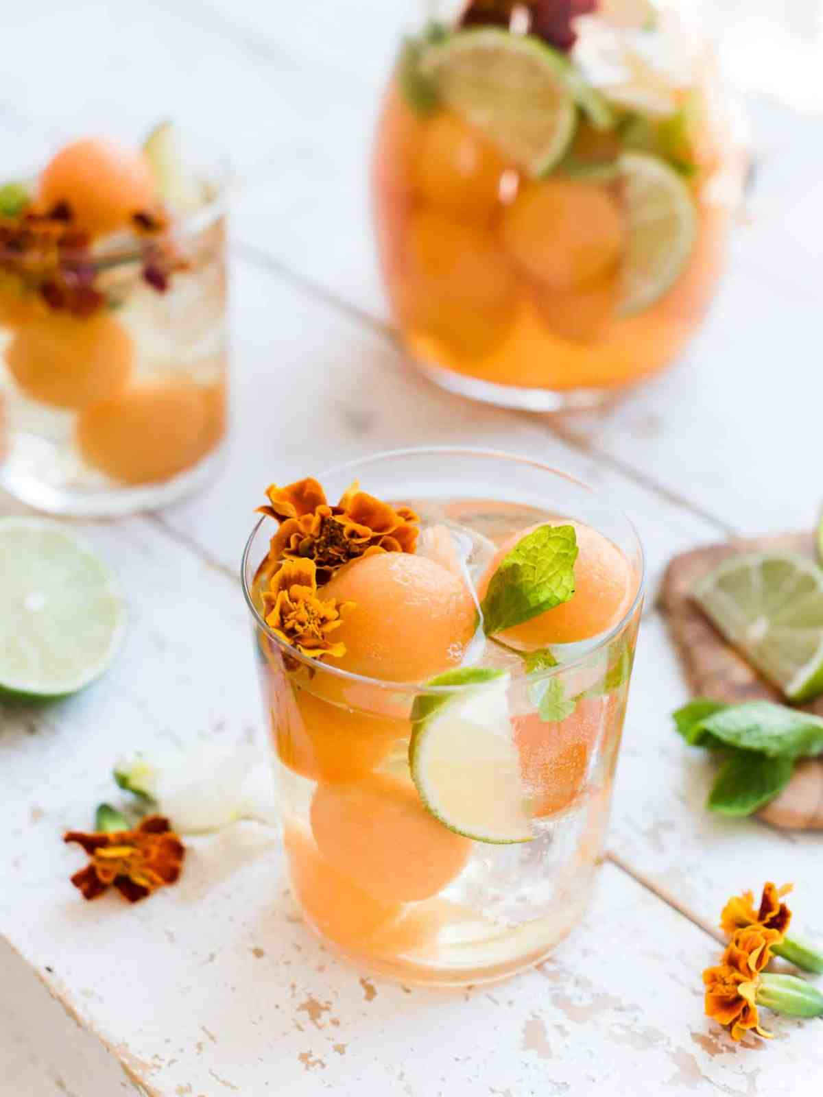 White sangria in a glass with cantaloupe, ginger, lime, mint and edible flowers.