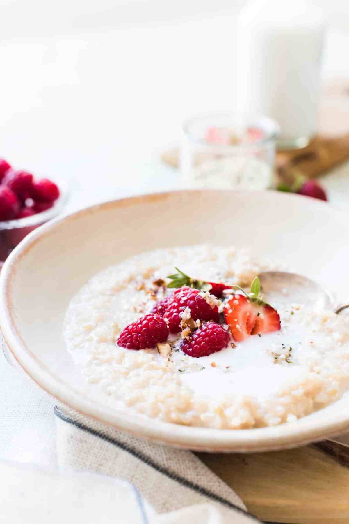 A bowl of Chai Coconut Brown Rice Pudding in bowl with fresh berries and coconut milk.