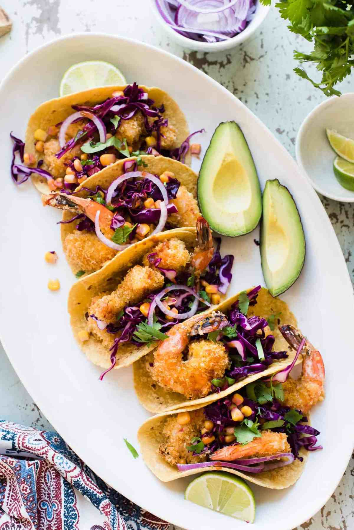 For the Oven-Fried Crispy Shrimp Tacos on a plate served with avocados.