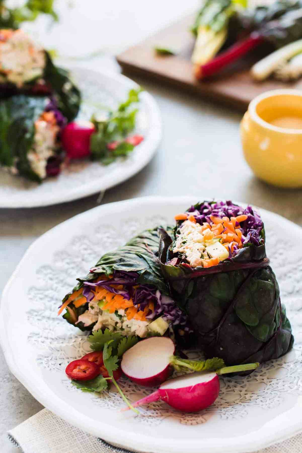 Thai-style chicken salad rainbow chard wraps on a white plate.