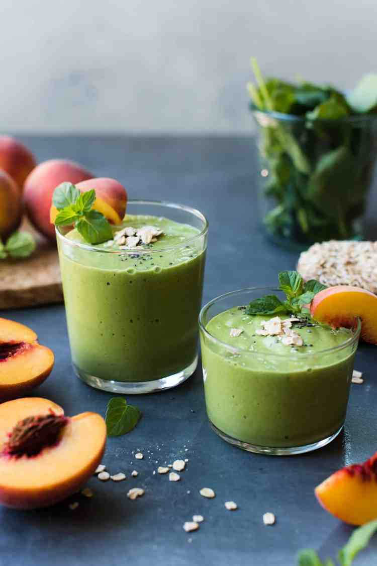 Glasses of Peaches and Cream Green Breakfast Smoothie with slices of peach and spinach in the background.