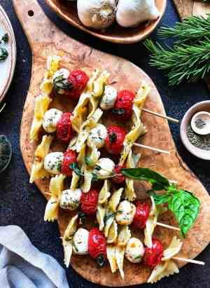 Roasted Tomato Caprese Skewers with pasta on a wooden cutting board.