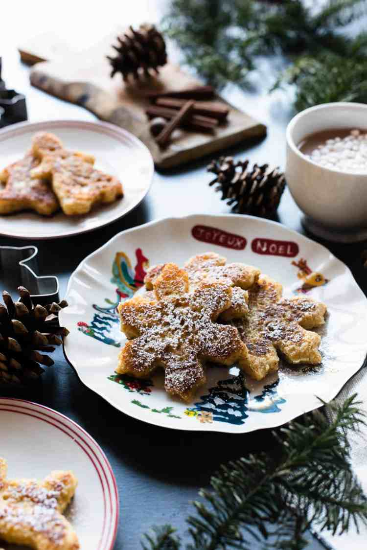 Gingerbread French Toast shaped like snowflakes on a holiday plate.