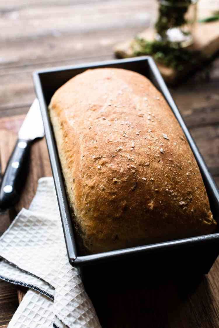Savory Herb Stuffing Bread in loaf pan on wooden table.