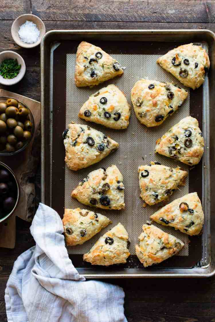 Savory Olive Cheese Scones on a baking tray on a wooden table with California Ripe Olives on the side.