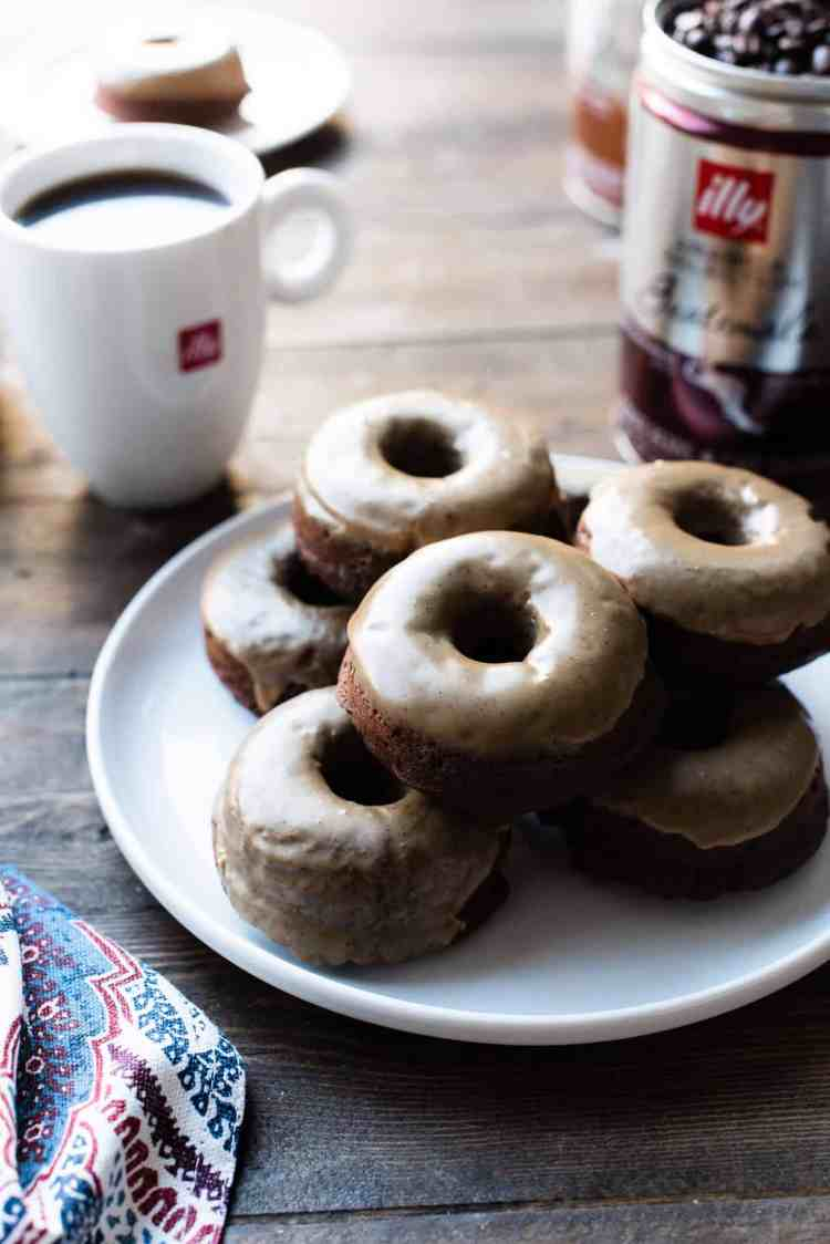 Stack of Coffee-Glazed Baked Chocolate Doughnuts on a white plate with illy coffee in the background.