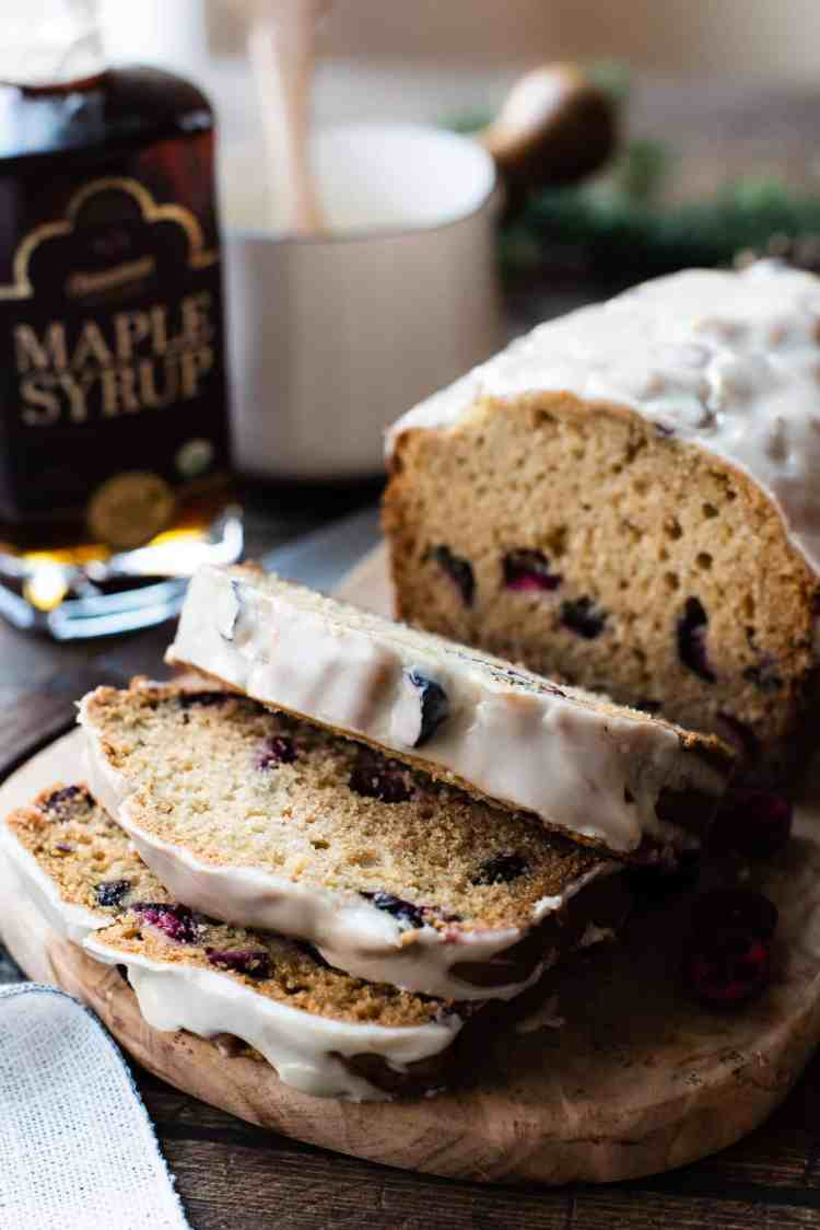 Maple-Glazed Cranberry Bread sliced on a cutting board with maple syrup in the background.