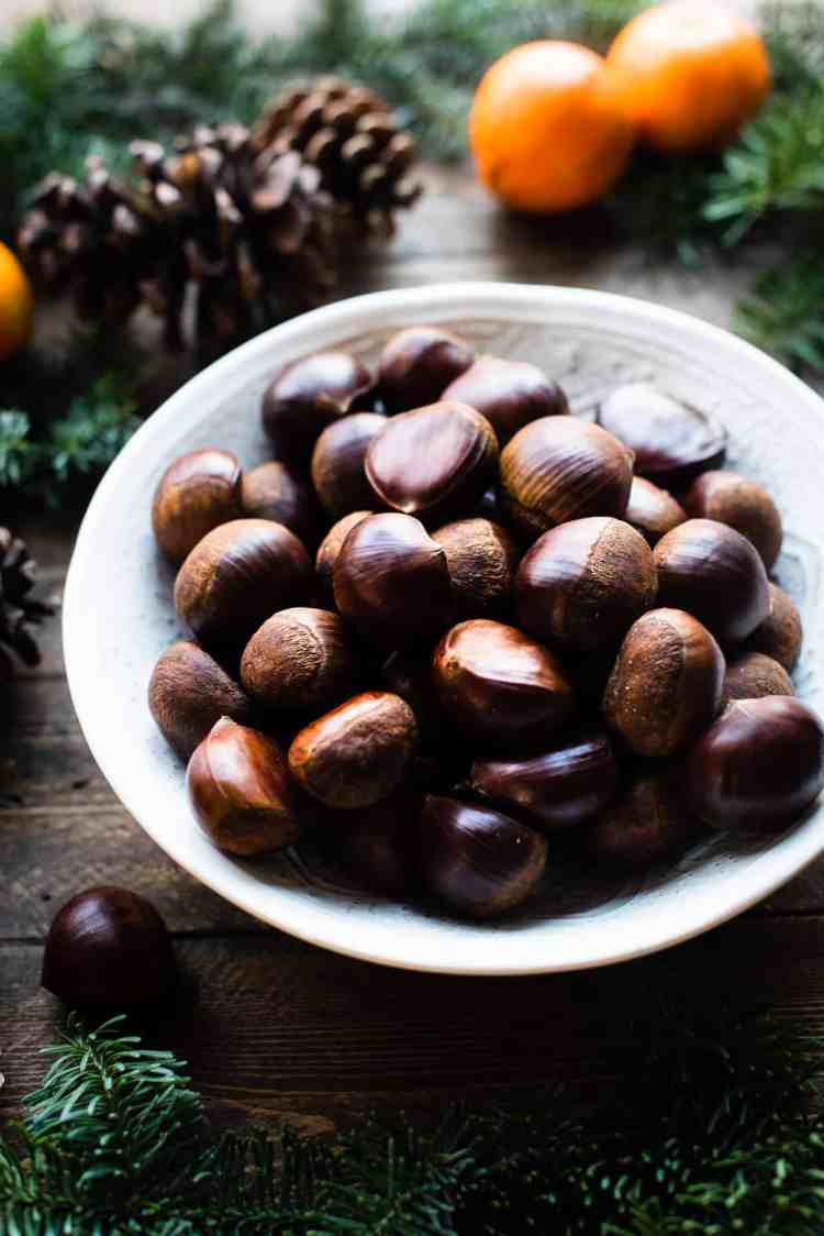 A bowl of chestnuts on a wooden table with evergreen, pinecones and oranges.