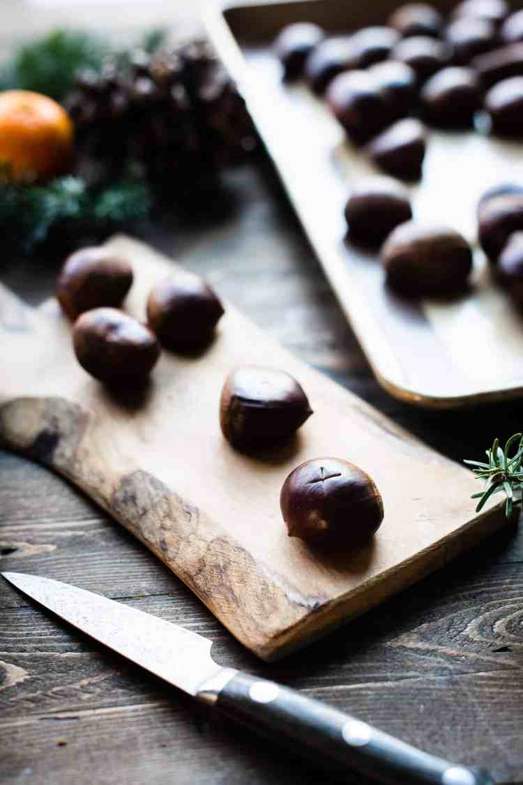Scoring oven roasted chestnuts with a knife on a wood board.