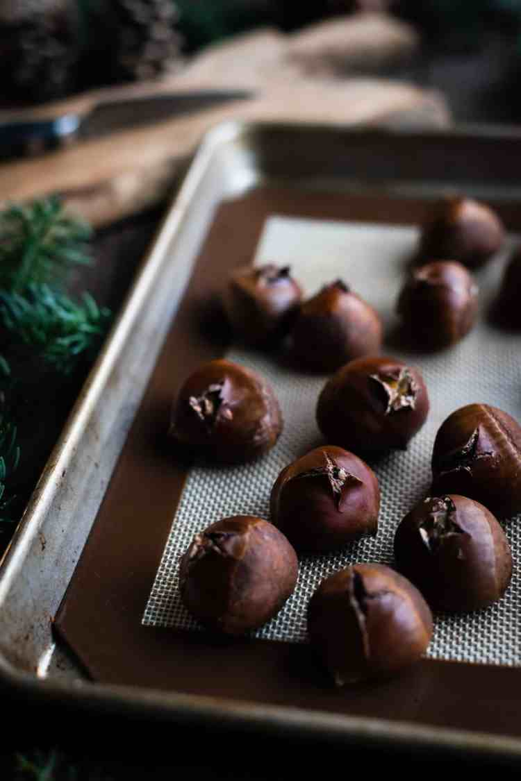Fresh oven-roasted chestnuts on a baking sheet.