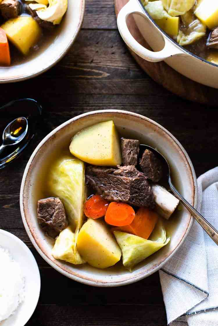 A bowl of Beef Nilaga (Filipino Beef and Vegetable Soup) made in the Instant Pot. Chunks of beef, short ribs, potato, cabbage, carrots, and sweet potato in a bowls.