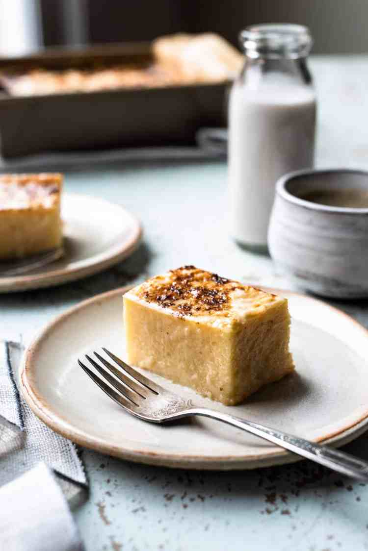 Slice of Cassava Cake on a cream plate with coffee and coconut milk in the background.