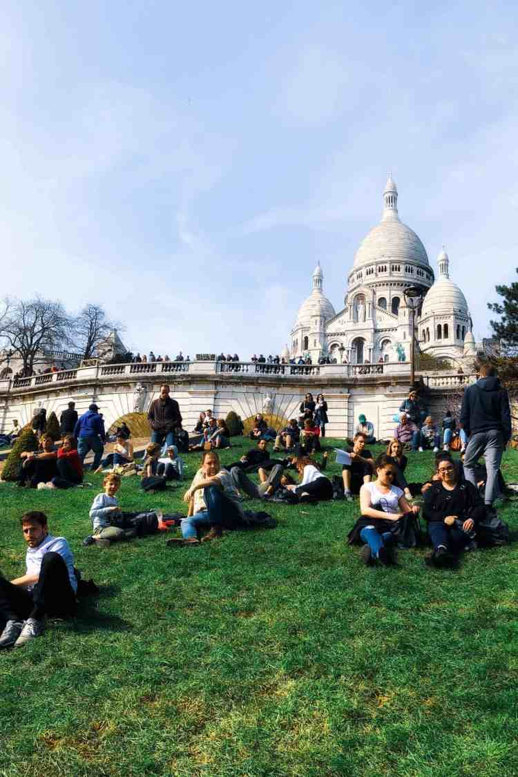 People resting on grass by Sacre Coeur.