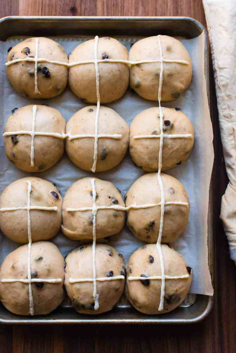 Hot cross buns with piped crosses ready for the oven.