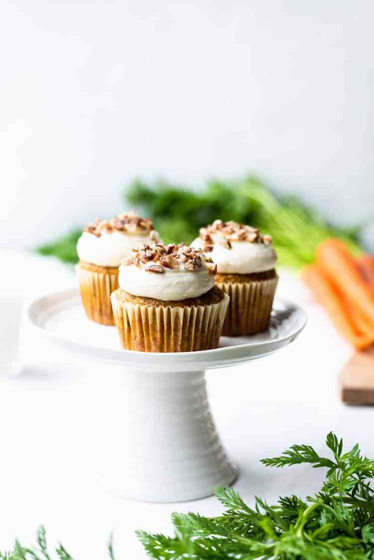 Vegan Carrot Cake Cupcakes on a small white cake stand with carrots in the background.