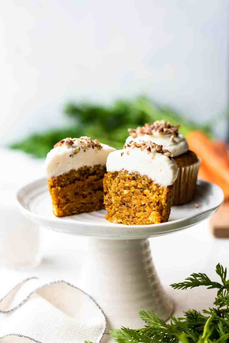 Carrot cake cupcakes with cream cheese frosting sliced in half on a cake stand.