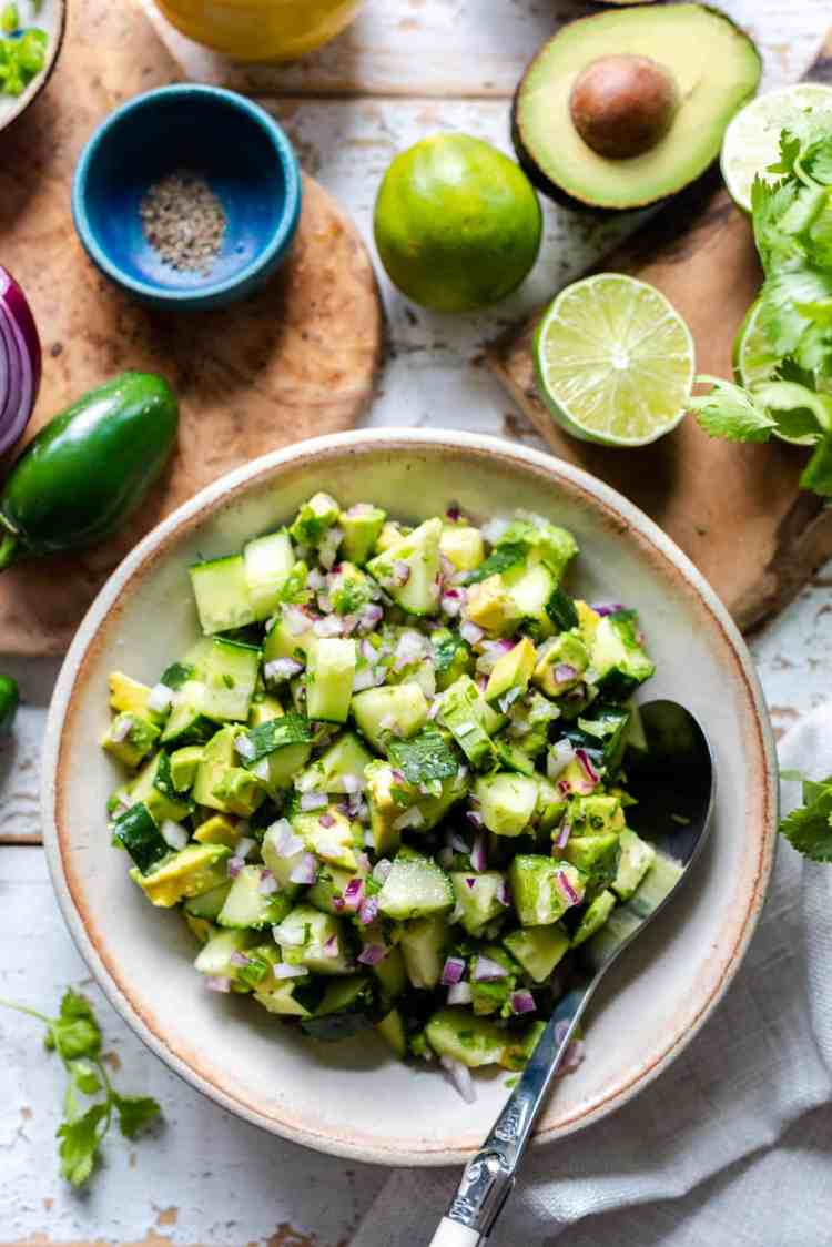 A bowl of Avocado Cucumber Salad with red onion, lime juice, and jalapeños.