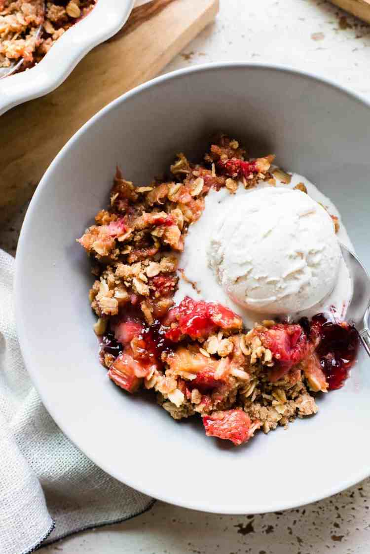Strawberry Rhubarb Crisp in a light gray bowl with a scoop of ice cream.