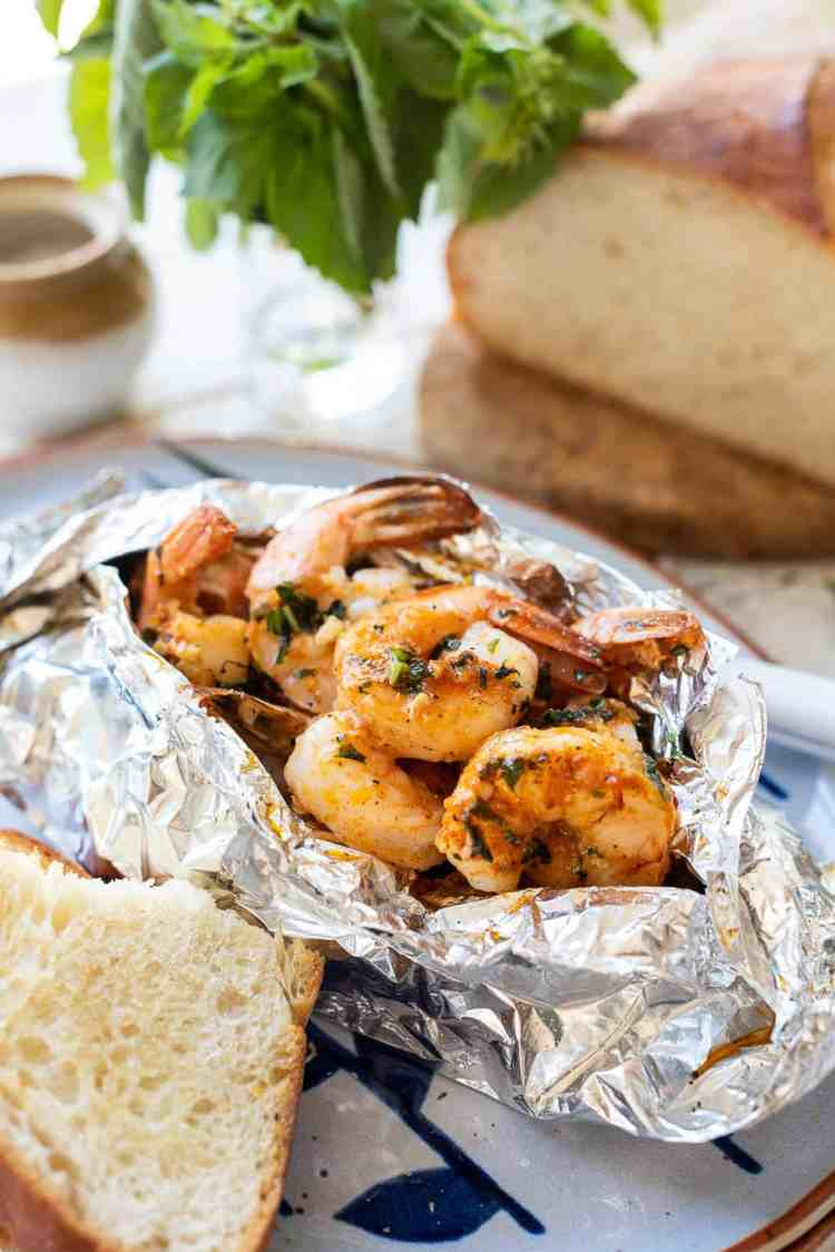 Grilled Shrimp Packets cook shrimp in a foil packet with herbed compound butter and bread on the side.