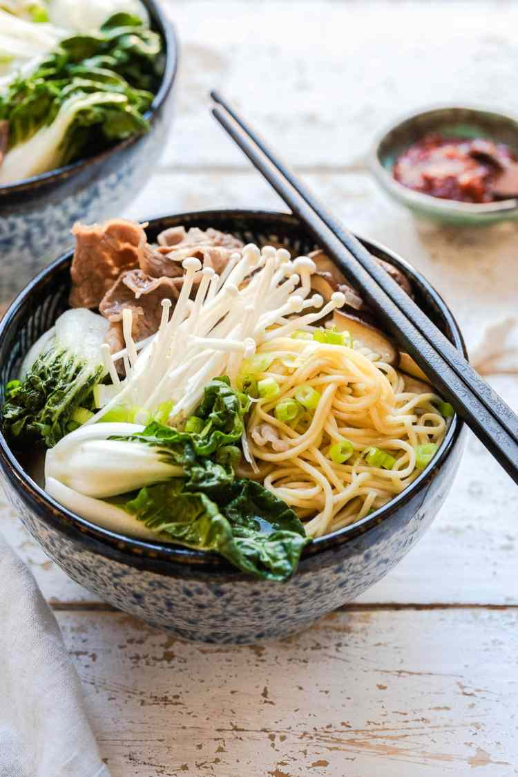 Mushrooma and Short Rib Noodle Soup in a blue bowl with chopsticks.