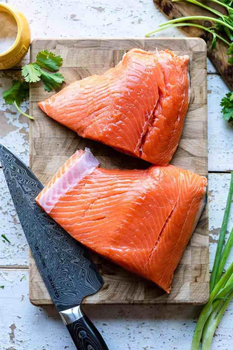 Alaska king salmon on a cutting board with a knife.