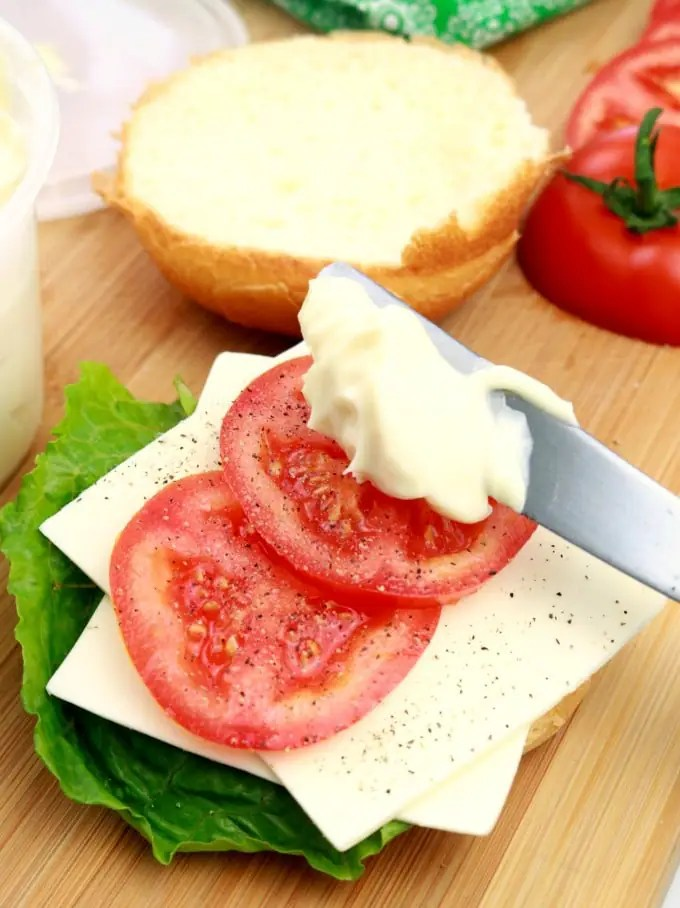Freshly made mayonnaise being spread over lettuce, tomatoes, and cheese on a brioche bun.