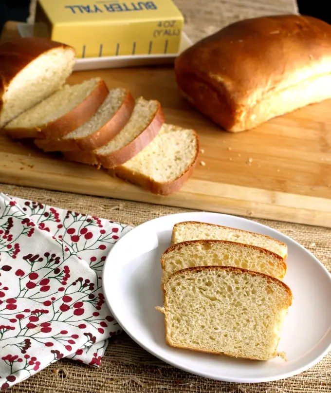a photo of Portuguese sweet bread whole loaf and a sliced loaf on a cutting board. In the front is a plate of sliced bread.