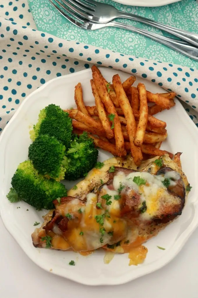 An overhead shot of Alice Springs Chicken on a white plate with broccoli and french fries. It is on a white table with teal pola-dotted and paisley napkins.
