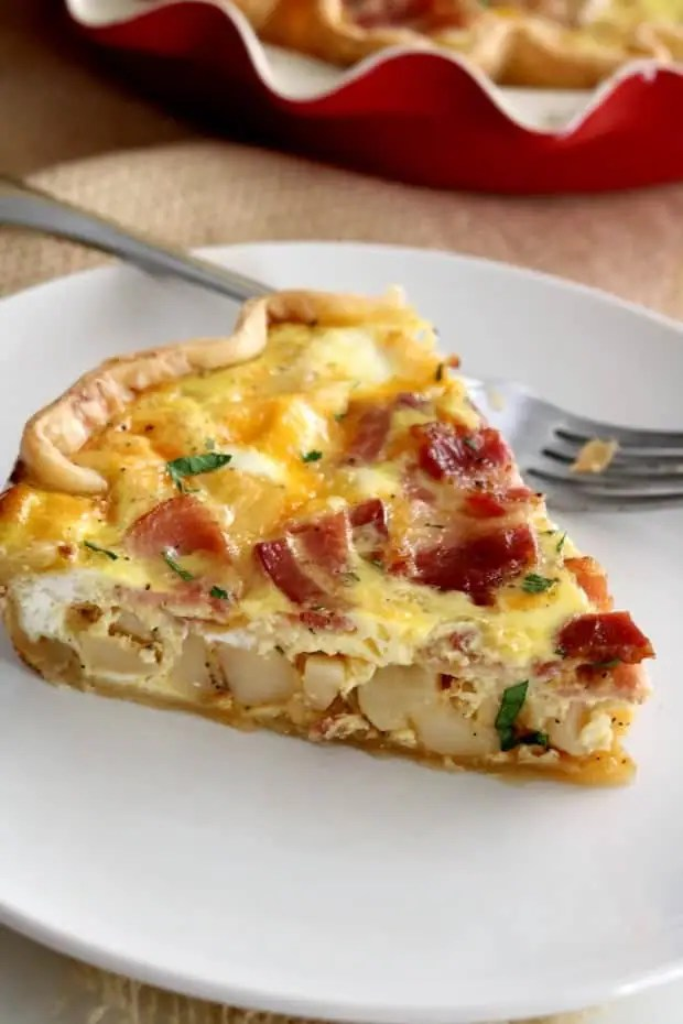 A close up photo of a slice of bacon and potato quiche.