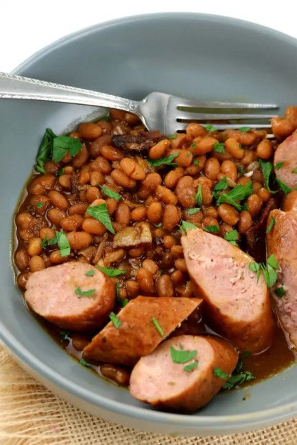 A bowl of boston baked beans with sausages