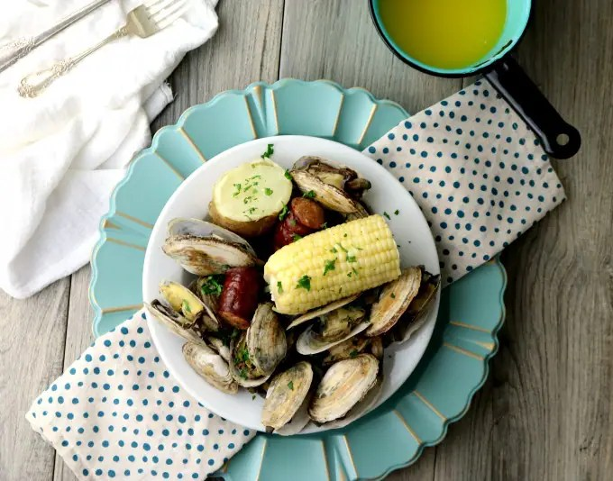 A horizontal image of a bowl of clams, sausage, and corn ready to be served.