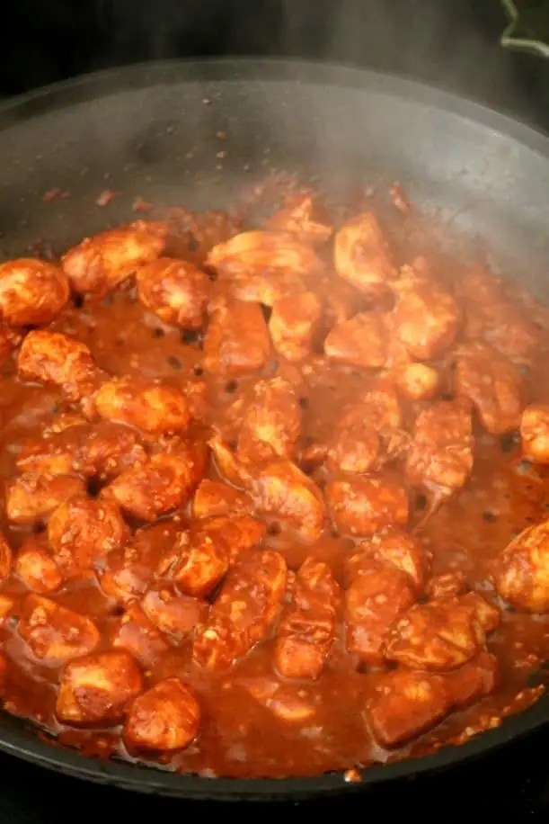 A skillet full of chicken vindaloo cooking on the stove top.