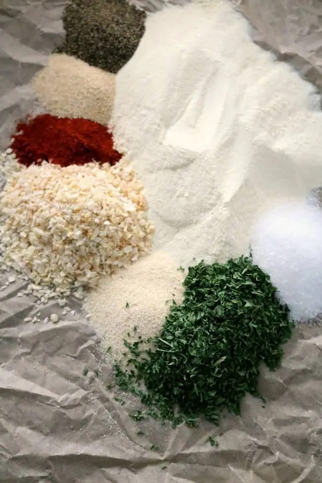 All the herbs and spices that go into ranch seasoning mix laid out on a piece of brown crumpled parchment paper.