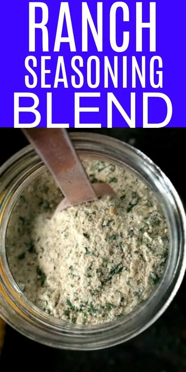 an overhead show of a jar of ranch seasoning mix with a gold tablespoon sticking out of the top.