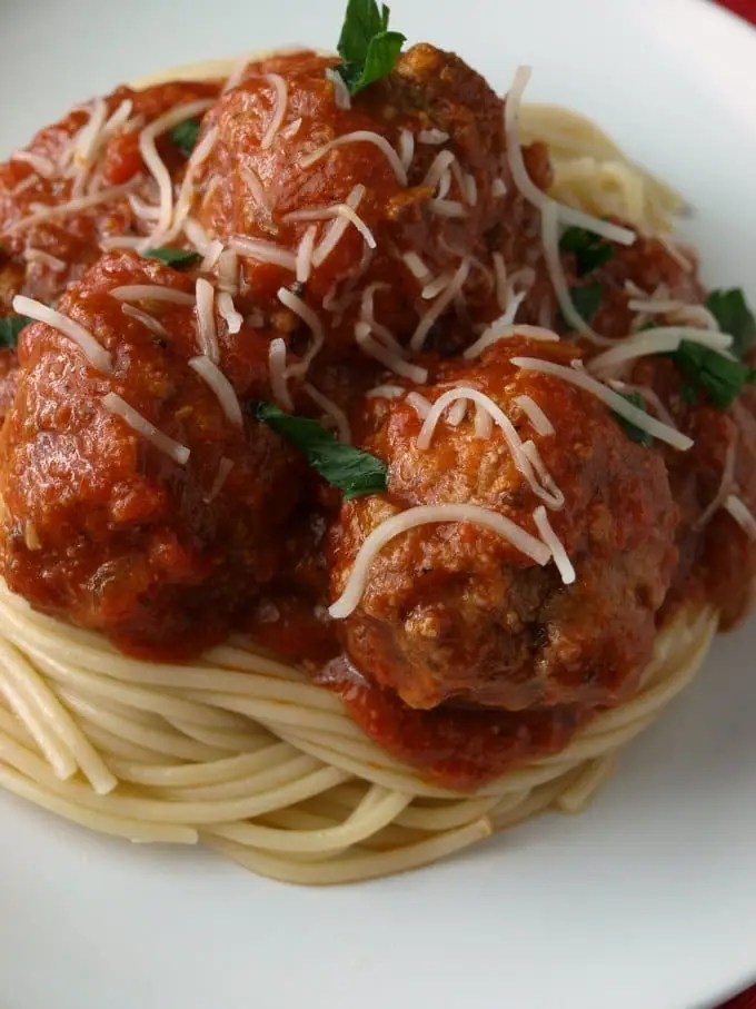 A close up photo of spaghetti and meatballs in marinara sauce on a white plate garnished with Parmesan cheese and torn basil.