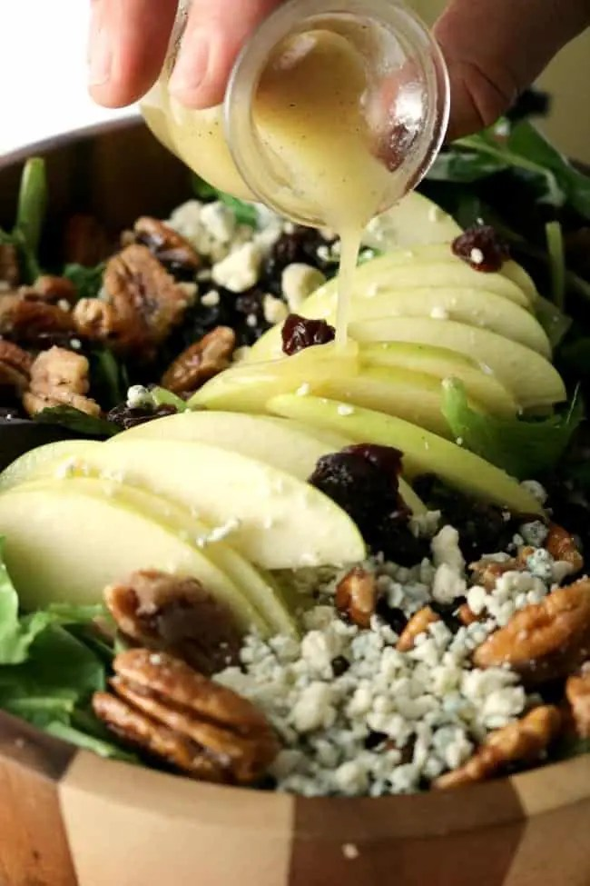Salad dressing being drizzled over the top of the Apple Pecan Blue Cheese Salad in a wooden bowl.