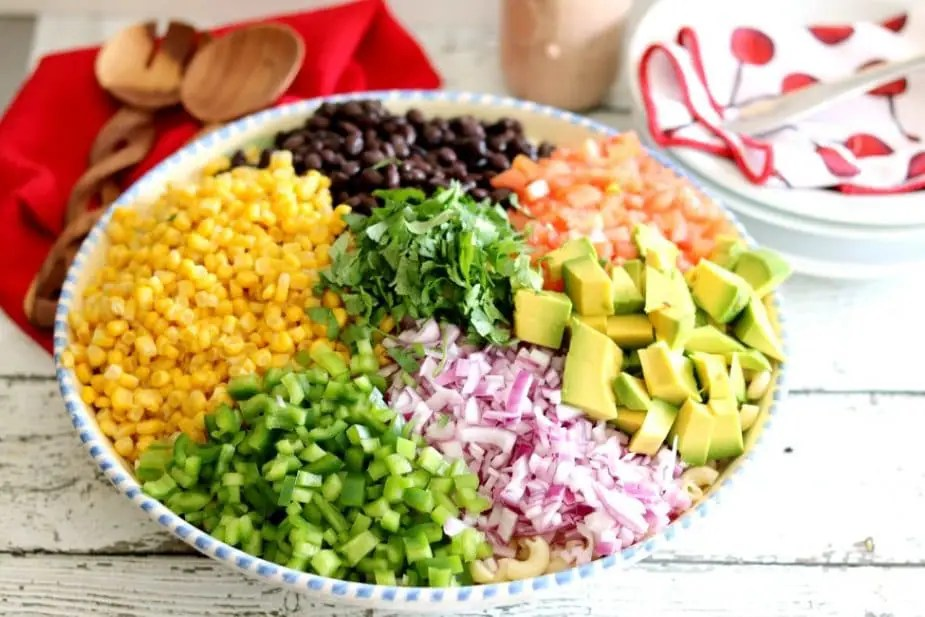 The ingredients for Mexican Macaroni salad in a bowl ready to be tossed with dressing.