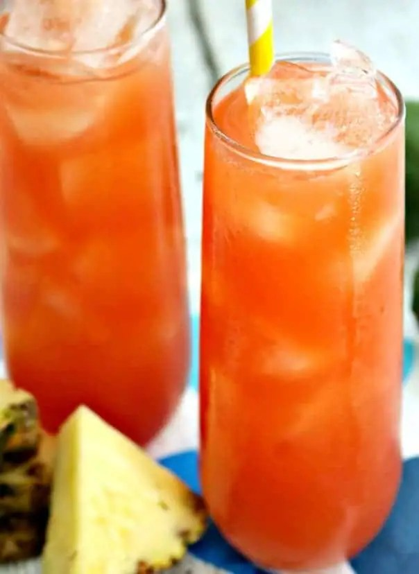 Two glasses of Caribbean Rum Punch with slices of fresh pineapple.