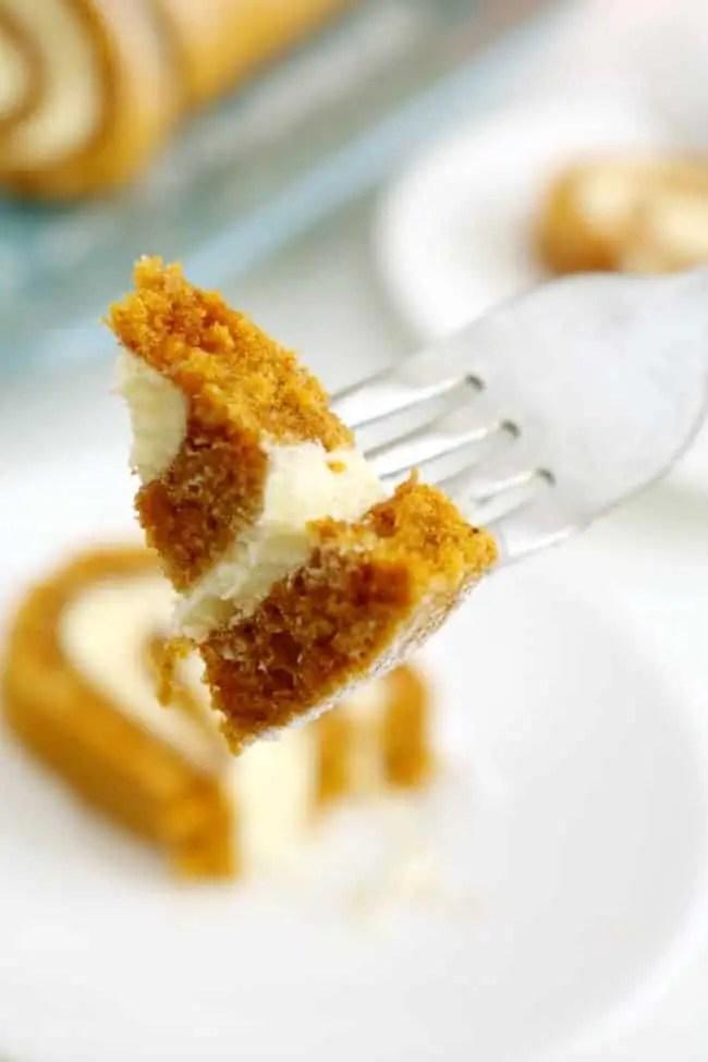 An up close show of a piece of pumpkin cake roll on a fork.