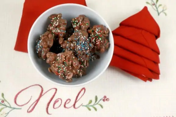 A bowl of slow cooker chocolate peanut clusters on a Noel placemat with a red napkin