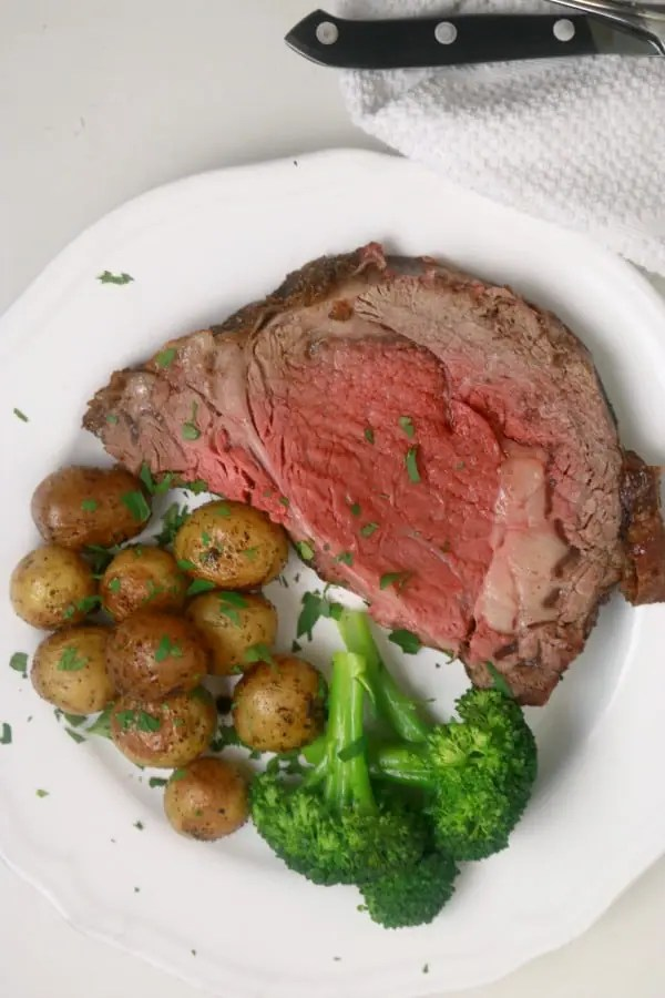 sliced prime rib on a plate with roasted potatoes and steamed broccoli.